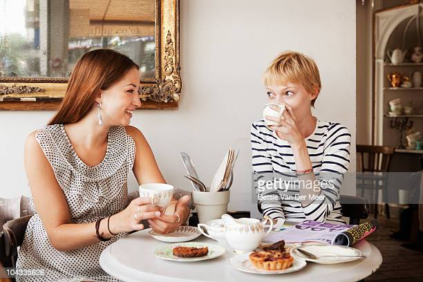 Female friends having tea and cakes in cafe.
