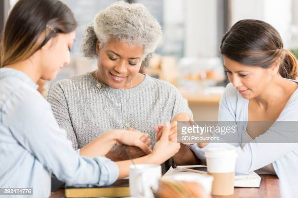 female friends hold hands while praying - christianity stock pictures, royalty-free photos & images