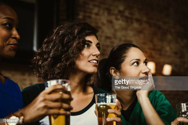 female friends holding beer glasses while watching soccer match in bar - mid adult women stock pictures, royalty-free photos & images