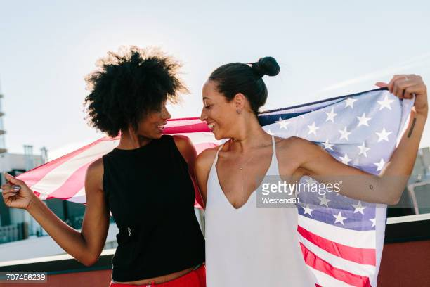 Female friends holding US American flag, standing on rooftop