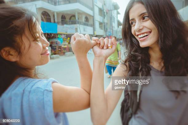 Female friends hooking pinky promise with little fingers.