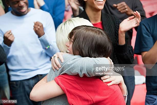 Amigas abrazándose en el partido de fútbol