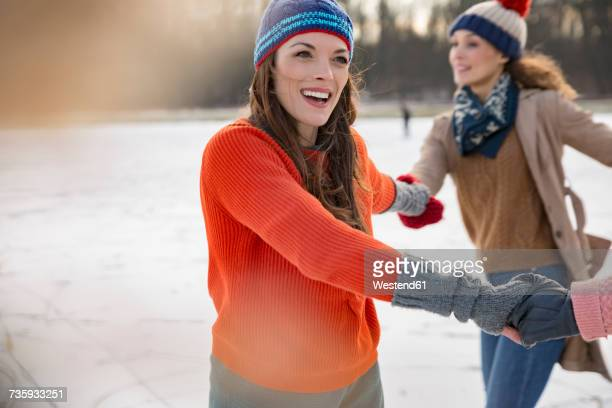 Female friends ice skating in a circle on frozen lake