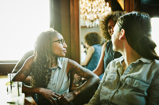 Female friends in discussion while hanging out in bar - gettyimageskorea
