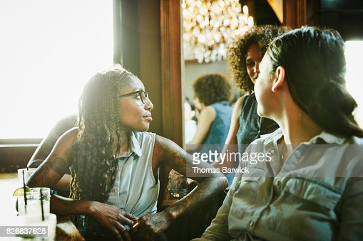 Female friends in discussion while hanging out in bar