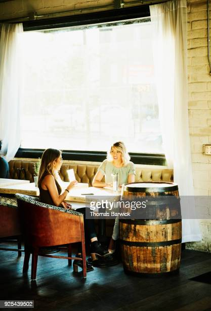 Female friends in discussion while sharing drinks in bar