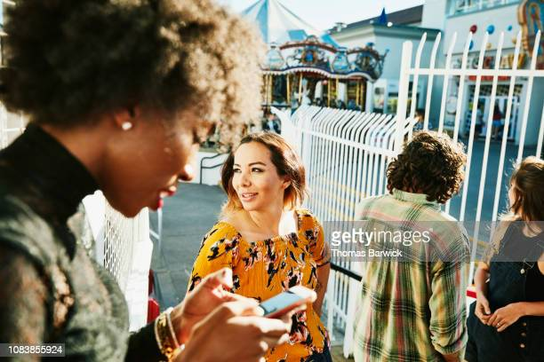 Female friends in discussion while waiting in line for ride at amusement park