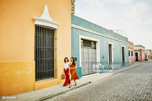 Female friends in discussion while walking through town while shopping on vacation