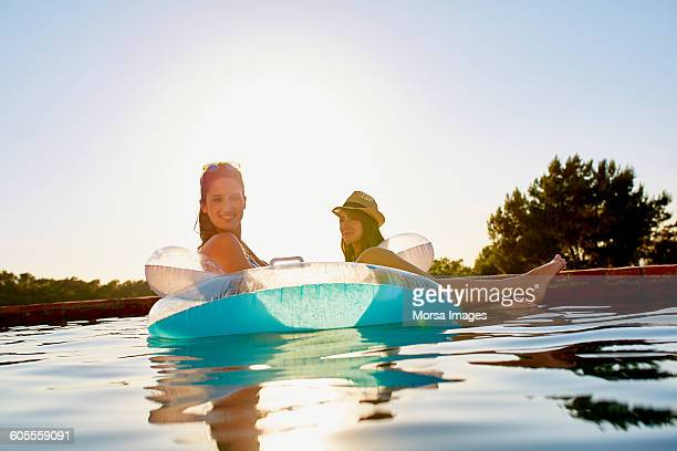 Female friends in inflatable ring floating on pool