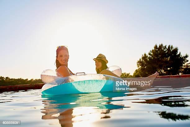 female friends in inflatable ring floating on pool - nur erwachsene stock-fotos und bilder
