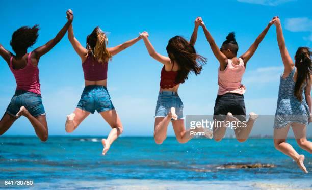 海と空に対してジャンプの女性の友人