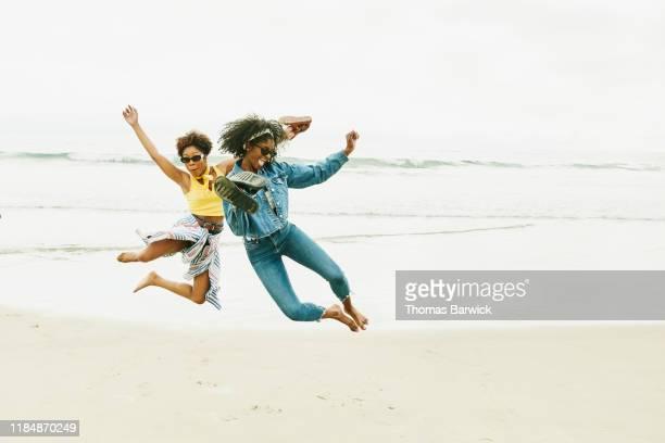 female friends jumping for joy during trip to beach - 25 29 anos imagens e fotografias de stock
