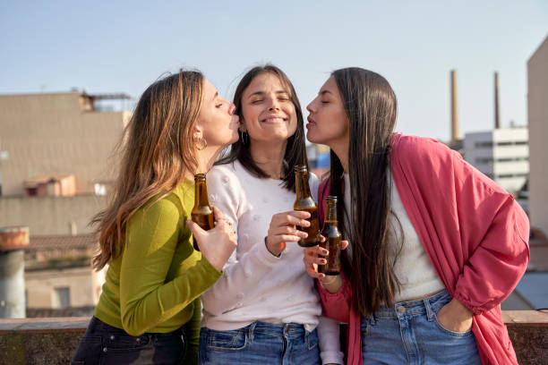 Female friends kissing young woman while drinking beer on rooftop