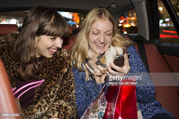 Female friends laughing and looking at mobile phone, sitting in back of taxi.