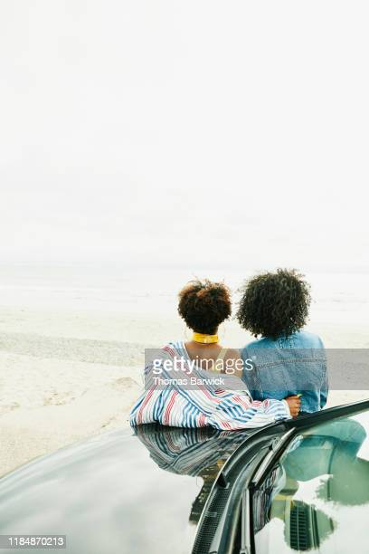 female friends leaning against hood of car and enjoying view of ocean - adults only stock pictures, royalty-free photos & images