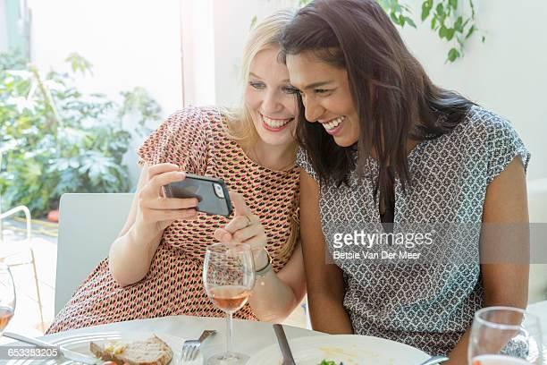 Female friends look at Selfies on phone.
