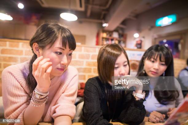 Female friends looking at menu in restaurant