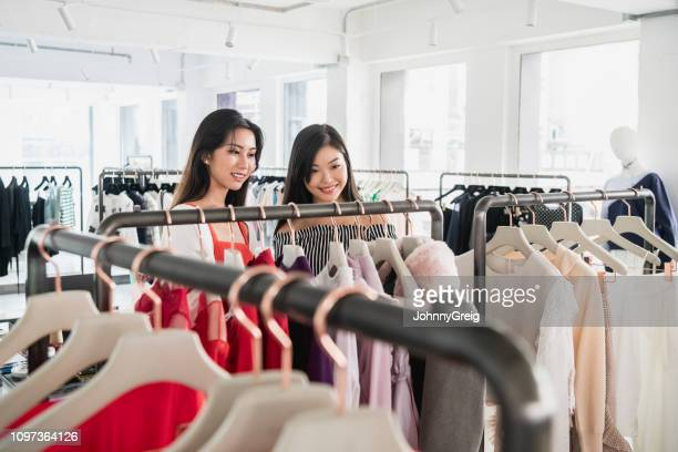 female friends looking at new clothes on rail - fashion hong kong stock photos and pictures