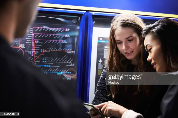 Female friends looking at smart phone while standing by illuminated map in subway station
