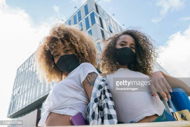 female friends looking at the camera in a portrait on the street while wearing their masks against covid 19 - social movement stock pictures, royalty-free photos & images