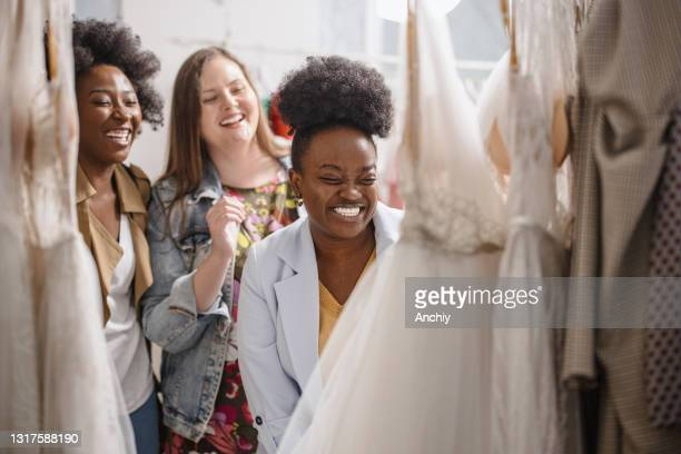 female friends looking at wedding dresses on rack - serbia stock pictures, royalty-free photos & images