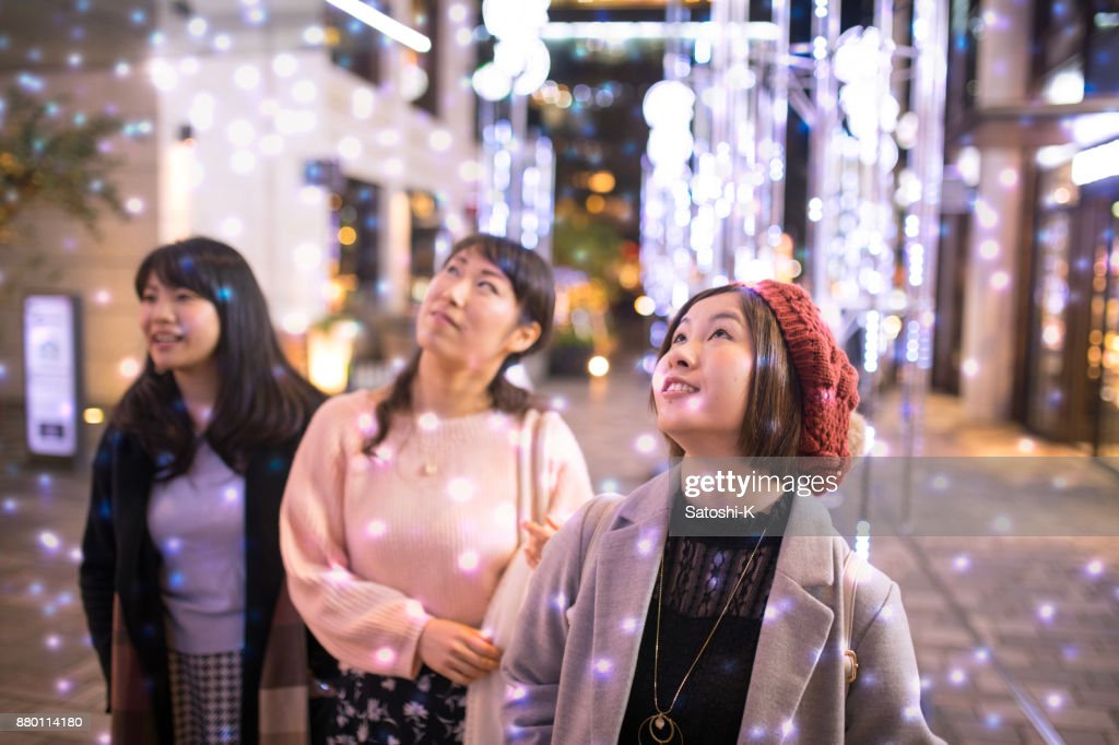 Female friends looking up in electrical snow white Christmas : Stock Photo
