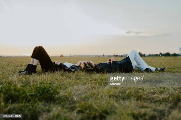 female friends lying down on grass in park - lying down stock-fotos und bilder