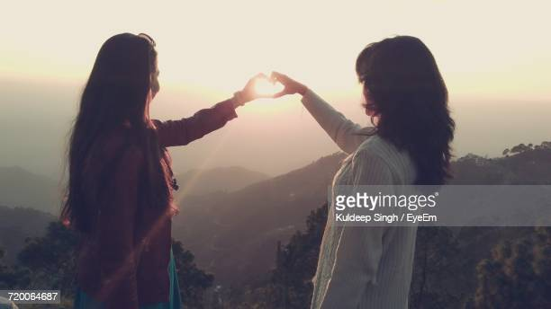 Female Friends Making Heart Shape From Hands In Front Of Sun Against Sky