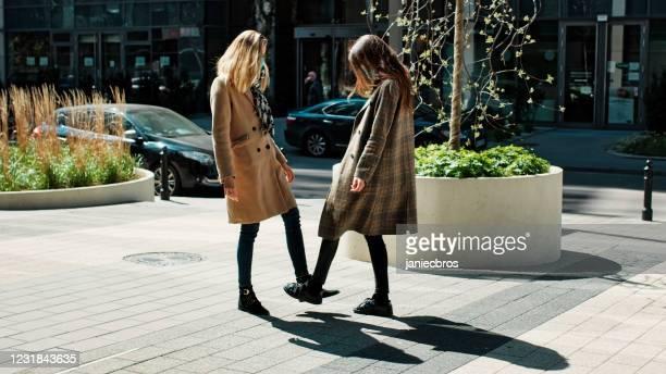 amis féminins se rencontrant pendant la pandémie de coronavirus. mise à pied - éviter de se serrer la main photos et images de collection
