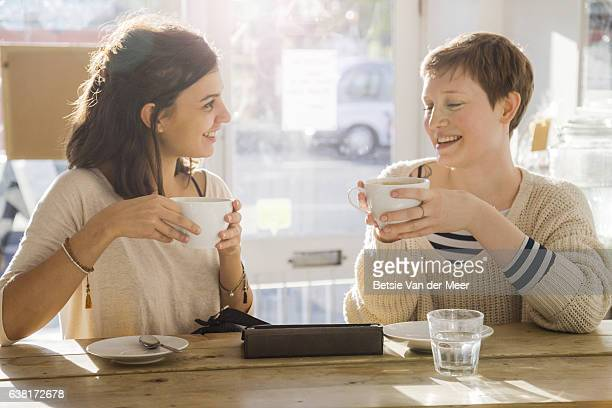 Female friends meeting up in cafe, drinking coffee and talking.