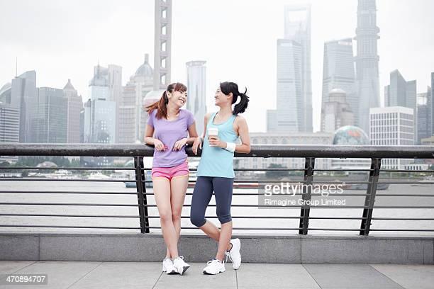 Female friends on bridge in Shanghai, China