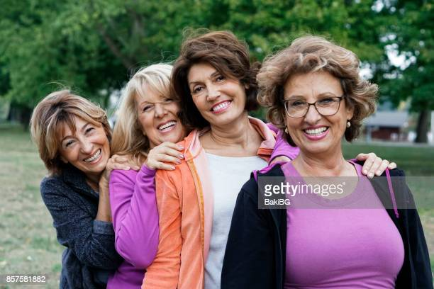 female friends over fifty exercising outdoors - donna 50 anni foto e immagini stock