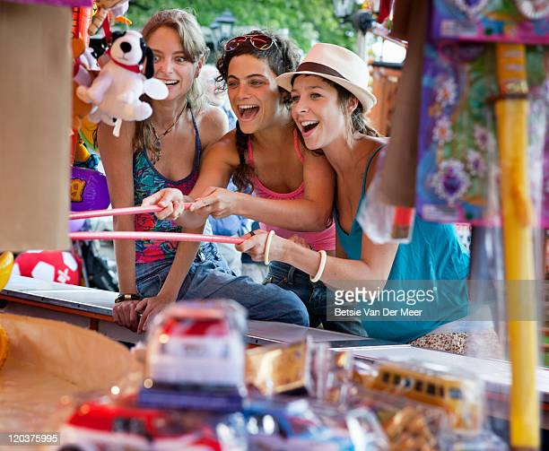 female friends playing game at funfair.
