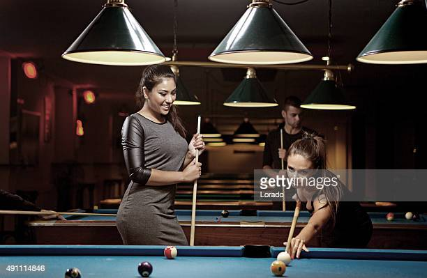 female friends playing pool