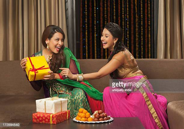female friends playing with gifts on diwali - diwali sweets stock photos and pictures