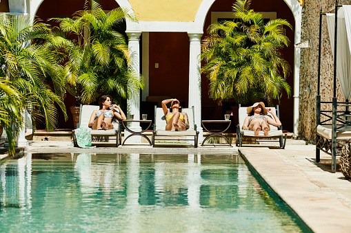 Female friends relaxing together in lounge chairs by pool in boutique hotel courtyard - gettyimageskorea