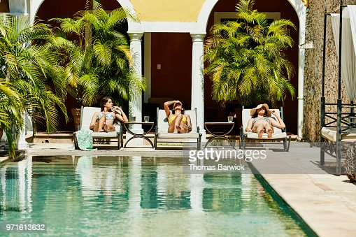 Female friends relaxing together in lounge chairs by pool in boutique hotel courtyard