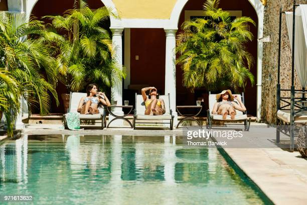female friends relaxing together in lounge chairs by pool in boutique hotel courtyard - poolside stock pictures, royalty-free photos & images