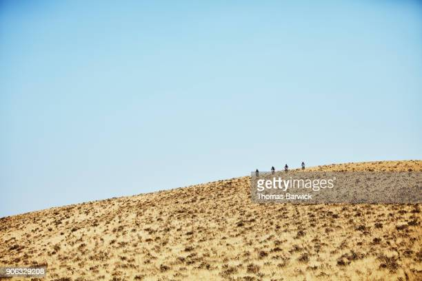 Female friends riding dirt bikes down hill while on desert ride