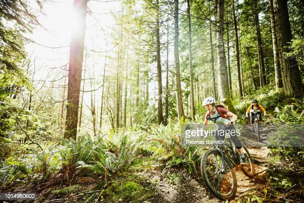 female friends riding mountain bikes down trail in wood - マウンテンバイク ストックフォトと画像