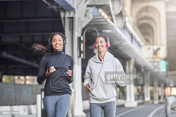 Female friends running on the city street