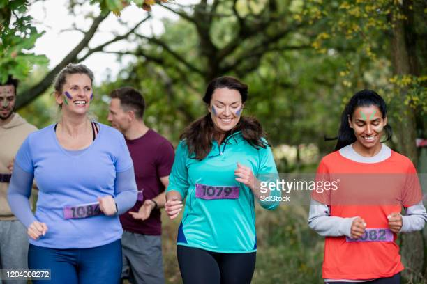 female friends running together in woodland for charity - competition group stock pictures, royalty-free photos & images