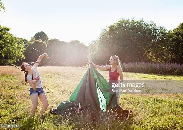 Female friends setting up a tent.