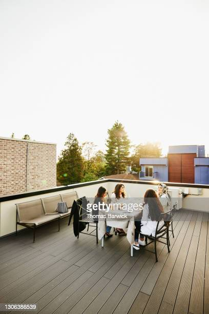 female friends sharing dinner on rooftop deck - four people stock pictures, royalty-free photos & images