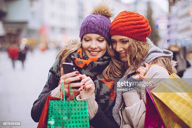 female friends shopping in city. - looking in bag stock pictures, royalty-free photos & images