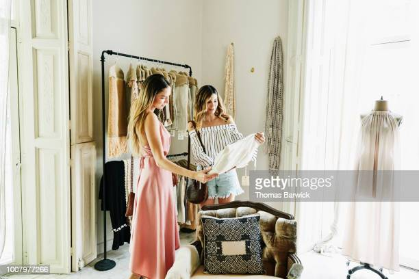 female friends shopping together in boutique - household equipment stock pictures, royalty-free photos & images
