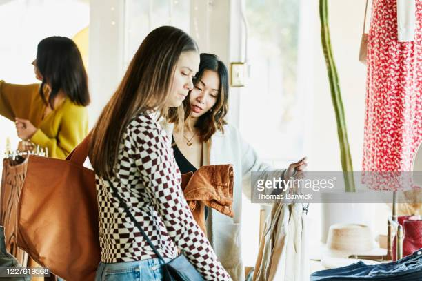 female friends shopping together in clothing boutique - western usa stock pictures, royalty-free photos & images