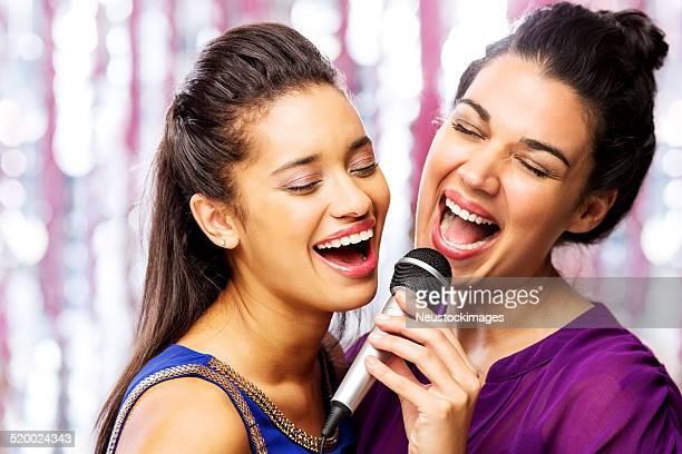 femininos amigos cantando karaokê no microfone em boate - karaokê - fotografias e filmes do acervo