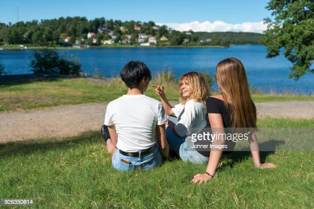 Female friends sitting at water