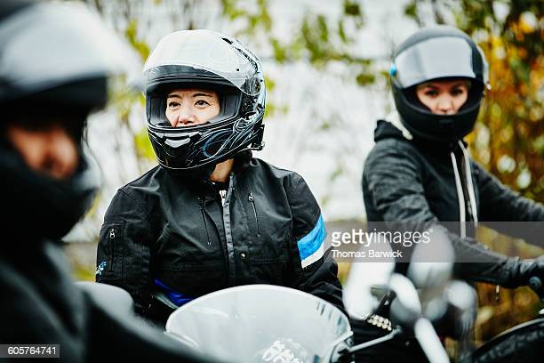 Female friends sitting on motorcycles before ride
